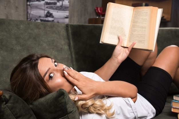 驚きの表情でソファで本を読んでいる若い女性。