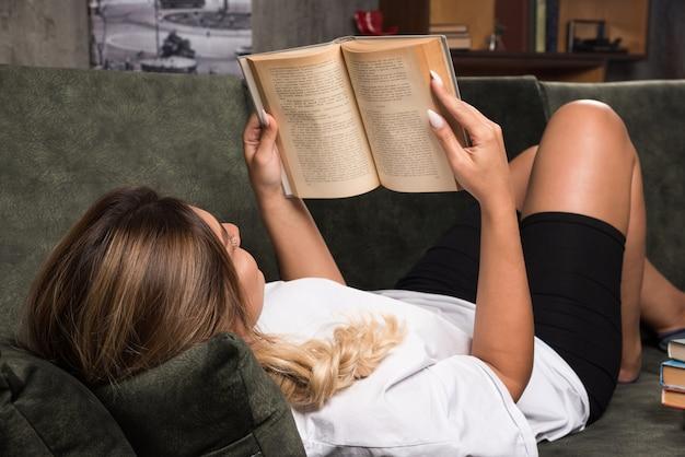 ソファで本を読んでいる若い女性。