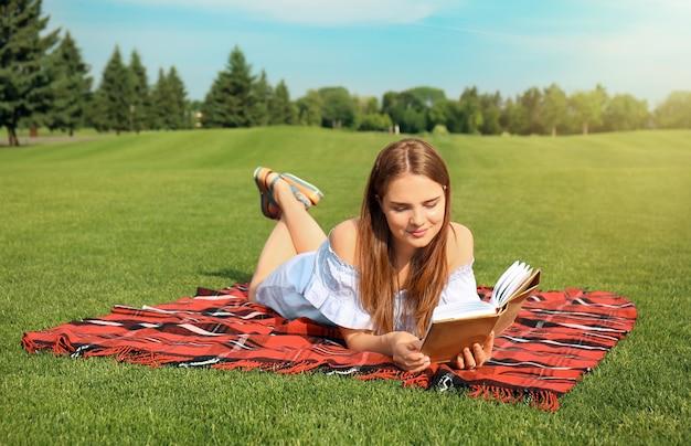 격자 무늬 야외에 책을 읽는 젊은 여자
