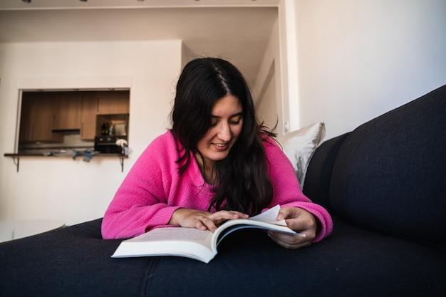 Молодая женщина, читающая книгу на диване