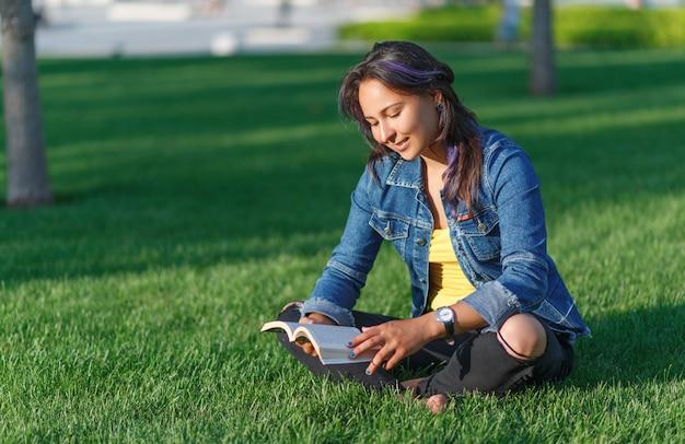 夏の公園で屋外の本を読んで若い女性