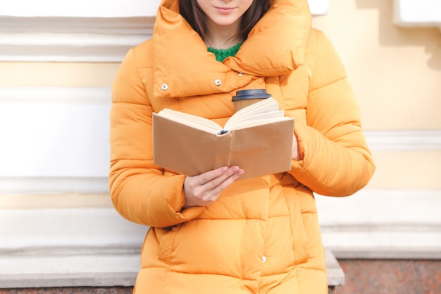 야외에서 책을 읽는 젊은 여자