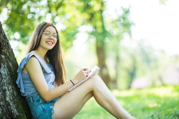 Giovane donna che legge un libro nel parco