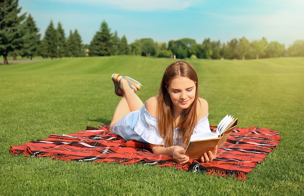 Young woman reading book on plaid outdoors