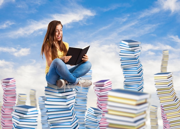 Young woman reading a book sitting on a books pile on the sky Free Photo
