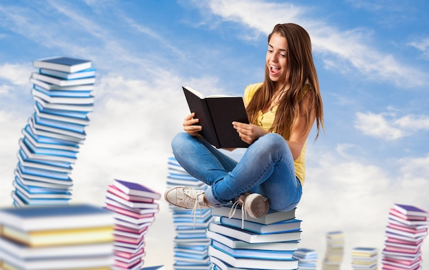 Young woman reading a book sitting on a books pile on the sky