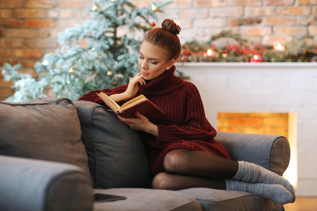 Young woman reading a book in the sofa