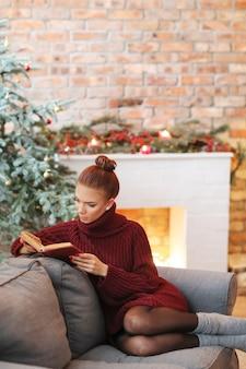 Giovane donna che legge un libro nel divano
