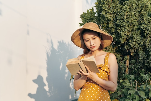 Young woman reading a book standing lean against trunk tree in summer park outdoor.