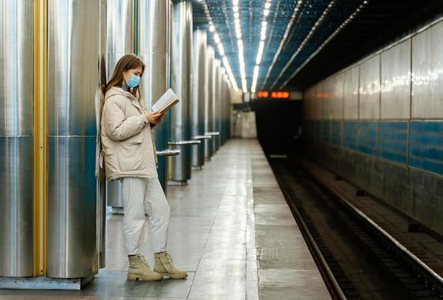 Giovane donna che legge un libro in una stazione della metropolitana