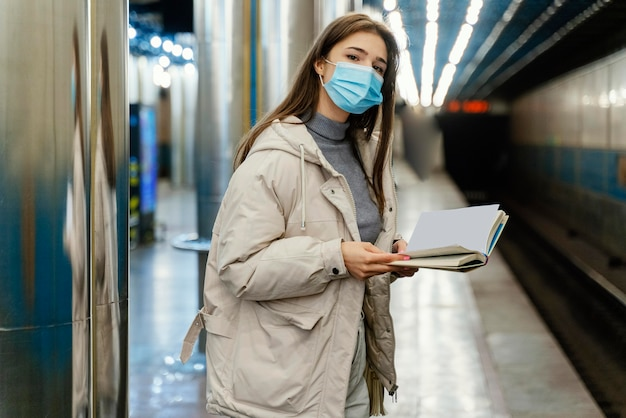 Young woman reading a book in a subway station