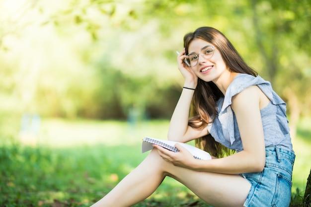 夕方の日光の下でピクニック中に木の下で本を読んで若い女性