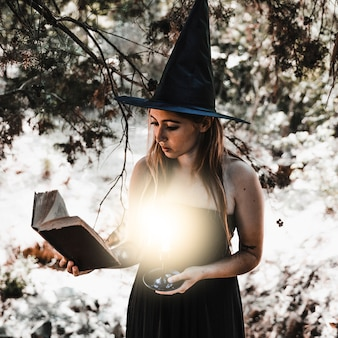 Young woman reading book with burning candle in woods