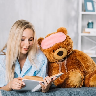 Young woman reading book with soft toy on bed