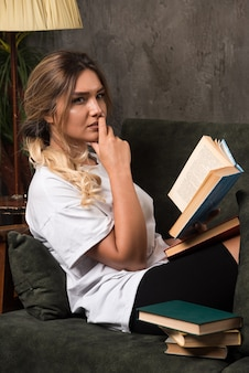 Young woman reading a book with thoughtful expression on couch.