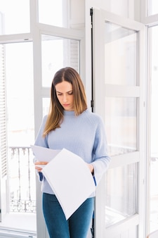 Young woman reading documents near window