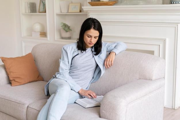 Giovane donna che legge un libro a casa