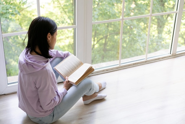 Young woman reading from a book at home