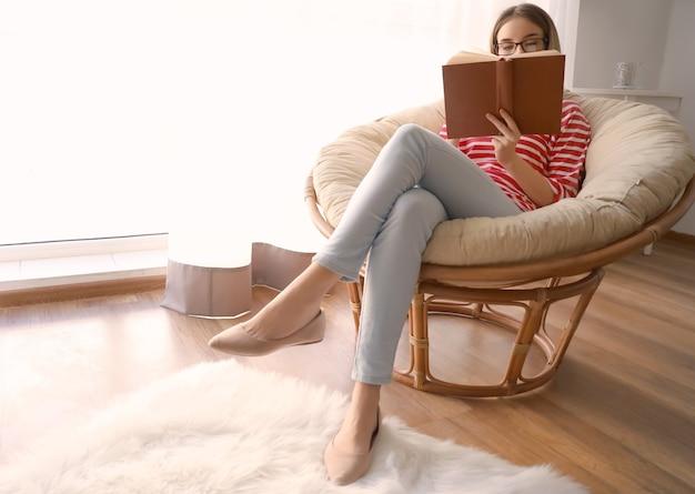 집에서 재미있는 책을 읽는 젊은 여자