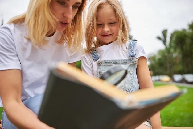 푸른 잔디에 귀여운 소녀에 대한 재미있는 책을 읽는 젊은 여자