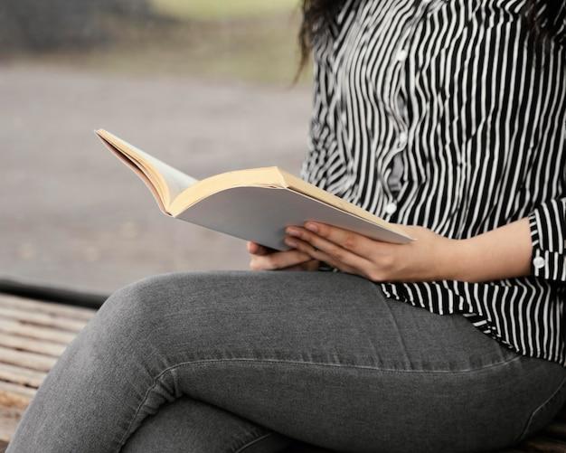 Giovane donna che legge un libro interessante all'aperto