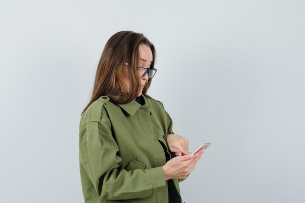 Молодая женщина читает новости по телефону в зеленой куртке, очках и смотрит сосредоточенно. передний план.