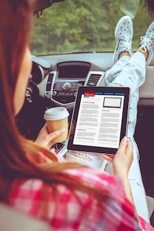 Молодая женщина читает новости с помощью планшета, сидя в carv