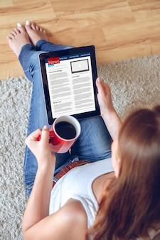 Молодая женщина читает новости с помощью планшета, сидя на диване у себя дома