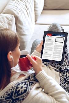 집에서 소파에 앉아있는 동안 태블릿을 사용하여 뉴스를 읽는 젊은 여자