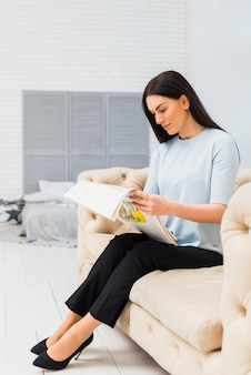 Young woman reading newspaper on couch
