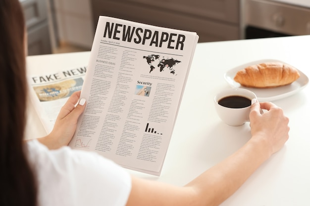 Young woman reading newspaper while drinking coffee in kitchen