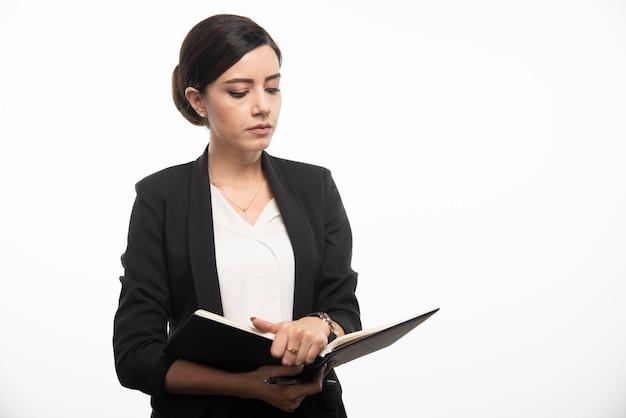 Taccuino della lettura della giovane donna su fondo bianco. foto di alta qualità