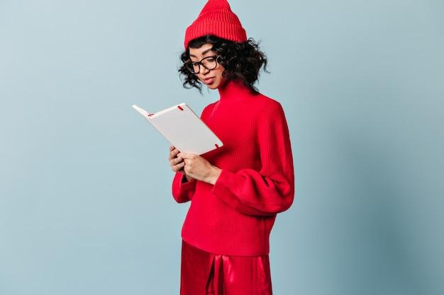 Молодая женщина читает тетрадь