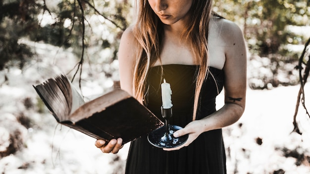 Young woman reading old book with candle in forest