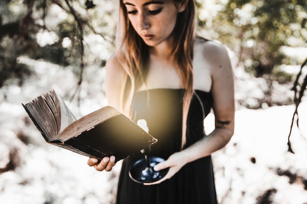 Young woman reading old book with candle in woods