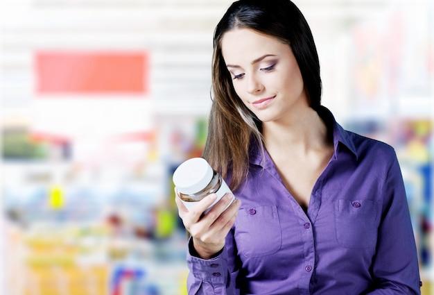 Молодая женщина, читающая на банке в супермаркете