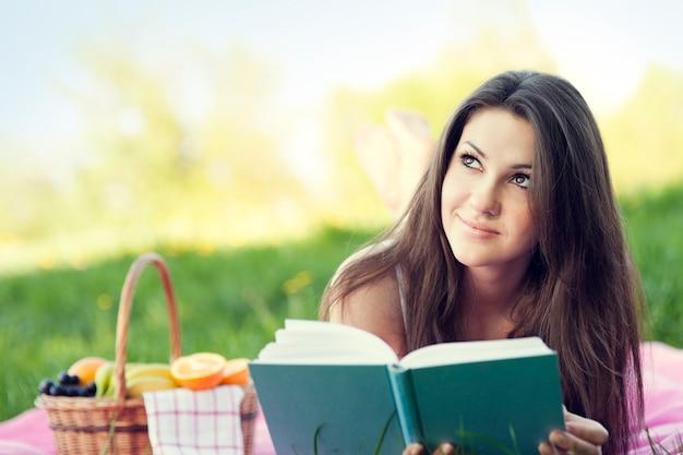 牧草地で読書若い女性