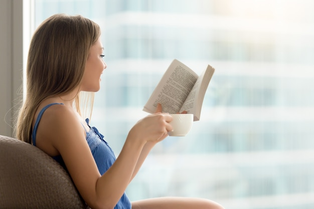 Young woman reading paper book in cafe with coffee