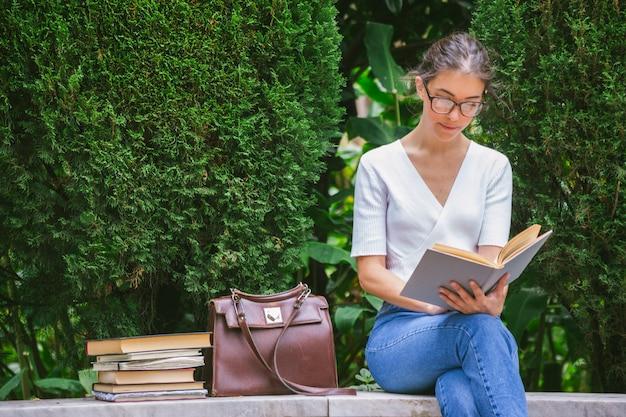 Молодая женщина читает литературу на улице