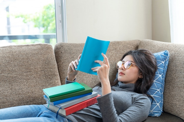 Young woman reading textbook on couch at home