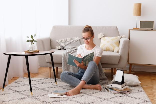 若い女性が居間で自宅で本を読む