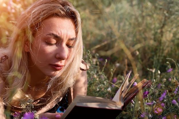 젊은 여자는 자연 여름 저녁에 들판에서 책을 읽습니다