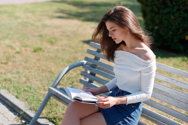 Young woman reads a book on a bench in a park on a summer day.