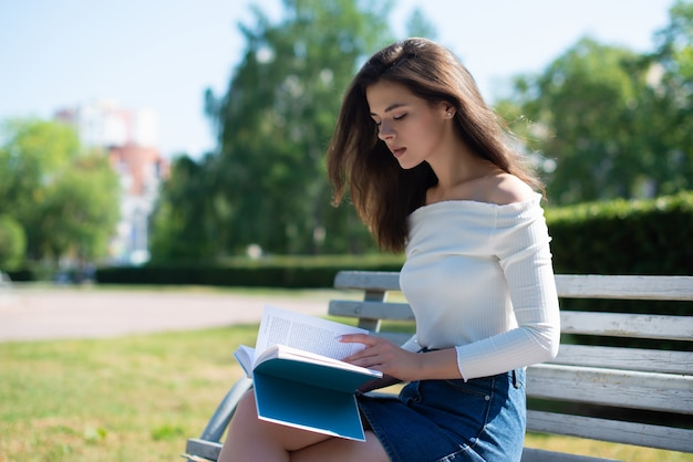 Young woman reads a book on a bench in a park on a summer day