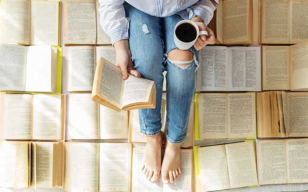 A young woman reads a book and drinks coffee. a lot of books.