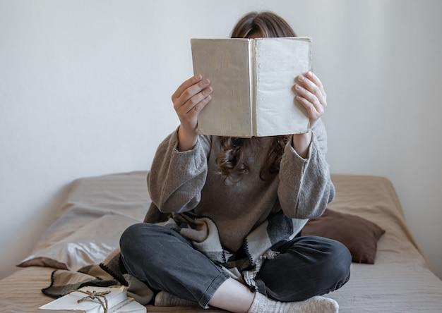 La giovane donna legge un libro mentre è seduta a letto