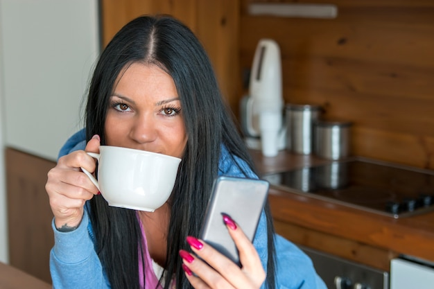 若い女性はコーヒーを飲みながら彼女のメッセージを読む