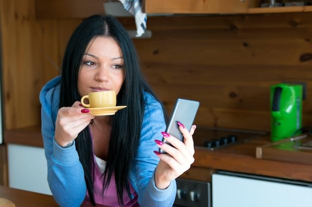 若い女性はコーヒーを飲みながら彼女のメッセージを読みます