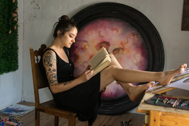 Young woman reads in her painting studio