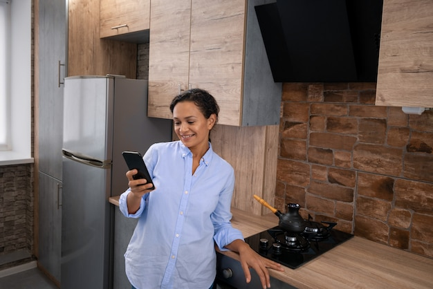 The young woman reads text messages in a smartphone while standing in the kitchen.